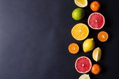 Vários tipos de citrinos em um fundo escuro Fotografia de Stock Royalty Free