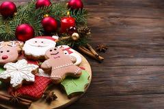 Vários tipos de cookies do pão-de-espécie do Natal com ramos de árvore do abeto, varas de canela, estrela do anis, vela e o ascen Fotos de Stock Royalty Free