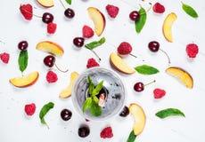 Vários tipos de frutos com folhas verdes e as bagas congeladas do cocktail no fundo de madeira branco Fotos de Stock Royalty Free