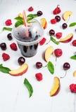 Vários tipos de frutos com folhas verdes e as bagas congeladas do cocktail no fundo de madeira branco Imagem de Stock Royalty Free