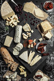 Vários tipos de queijo com especiarias, vidros de vinho e fatias diferentes do pão no fundo vazio do espaço Fotografia de Stock Royalty Free