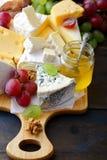 Vários tipos de queijo com uvas, mel e nozes na placa de corte Imagem de Stock Royalty Free