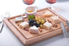Vários tipos de queijo, de mel e de uvas Imagem de Stock Royalty Free