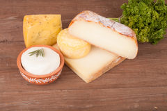 Vários tipos de queijo em um fundo de madeira com salsa Imagens de Stock