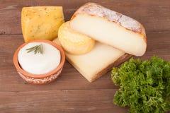 Vários tipos de queijo em um fundo de madeira com salsa Fotos de Stock