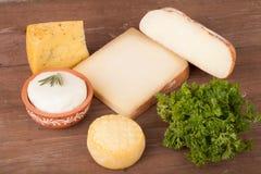 Vários tipos de queijo em um fundo de madeira com salsa Imagem de Stock