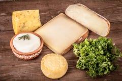 Vários tipos de queijo em um fundo de madeira com salsa matiz Fotos de Stock Royalty Free