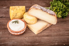 Vários tipos de queijo em um fundo de madeira com salsa matiz Foto de Stock