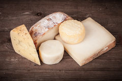 Vários tipos de queijo em um fundo de madeira matizado Imagens de Stock