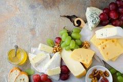 Vários tipos de queijos com uvas, mel, pão e nozes no fundo da ardósia Fotos de Stock Royalty Free