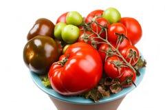 Vários tipos de tomates em uma bacia na tabela Imagens de Stock Royalty Free