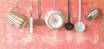 Vários utensílios da cozinha do vintage em uma parede rústica Imagens de Stock