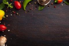 Vários vegetais e ervas na tabela de madeira escura Imagens de Stock