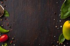 Vários vegetais e ervas na tabela de madeira escura Foto de Stock