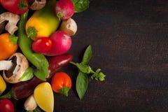 Vários vegetais e ervas na tabela de madeira escura Fotografia de Stock Royalty Free
