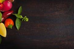 Vários vegetais e ervas na tabela de madeira escura Foto de Stock Royalty Free