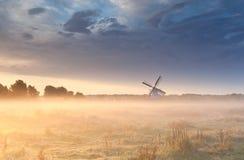 Väderkvarn i dimma på soluppgång Arkivfoton