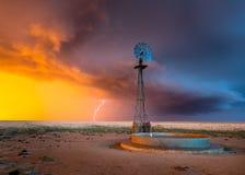 Väderkvarn i en åskväder på solnedgången Arkivfoton