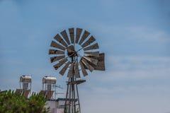 Väderkvarn i en stadsmiljö med blå himmel royaltyfri fotografi