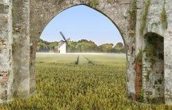 Väderkvarn i ett vetefält till och med en valvgång arkivfoton