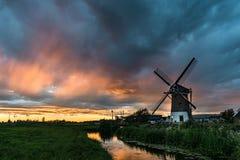 Väderkvarn i gouda, Holland längs en kanal med en färgrik solnedgång arkivbilder