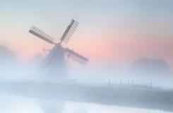 Väderkvarn i tät dimma på sommarsoluppgång Arkivfoto