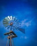 Väderkvarn med blå molnig himmel Arkivfoto