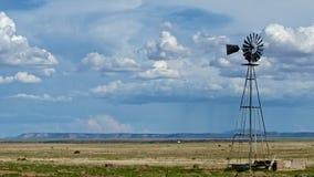 Väderkvarn med en avlägsen vindlantgård Royaltyfri Fotografi