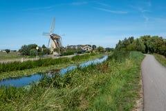 Väderkvarn och lantgård längs kanalen på en fördämning nära Maasland, net royaltyfri foto