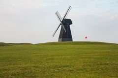 Väderkvarn och röd flagga med grön gräsmatta och mulen himmel royaltyfria foton