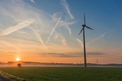 Väderkvarn på ett skördfält, soluppgång i bakgrunden arkivbild