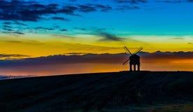 Väderkvarn på solnedgången, skys på brand som är härlig arkivbilder