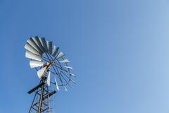 Väderkvarn som kura ihop sig i en blå himmel Arkivfoto