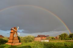 Väderkvarn under regnbågen royaltyfria bilder