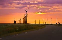 Väderkvarnar framme av den ljusa solnedgången Royaltyfria Foton