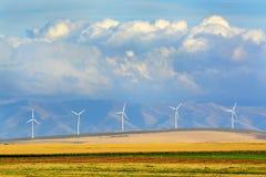 Väderkvarnar i rader med bergmoln och fält Arkivfoto