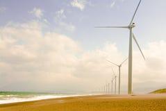 Väderkvarnar längs stranden Royaltyfri Bild