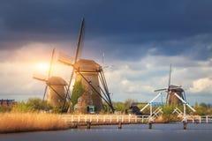 Väderkvarnar mot molnig himmel på solnedgången i Kinderdijk, Netherland Royaltyfria Bilder