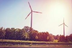 Väderkvarnar på för maktenergi för solnedgång det elektriska industriella alternativet Arkivbild