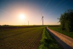 Väderkvarnar på solnedgången i fälten Fotografering för Bildbyråer