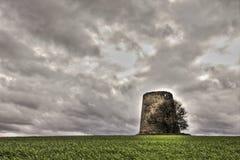 Väderkvarnen fördärvar in framme av en dramatisk himmel Royaltyfri Foto