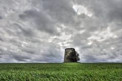 Väderkvarnen fördärvar in framme av en dramatisk himmel Arkivbild