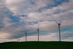Väderkvarnturbinerna är närbilden mot bakgrunden av solnedgångmoln royaltyfria foton