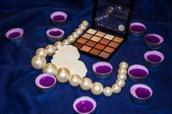 Vädrade stearinljus, en palett av skuggor, en hjärta och härliga pärlor på en filt royaltyfria foton