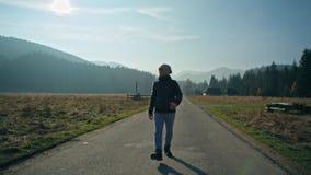 Väg av den unga mannen som går på vägen i bygd i nedgång med berg och himmel arkivfilmer