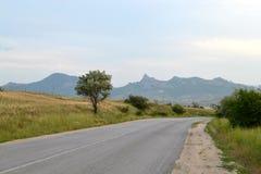 Väg berg, gräs, himmel Arkivfoto