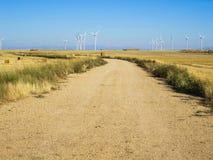 Väg bland sädes- fält och vindturbiner Royaltyfria Bilder