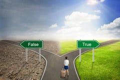 Väg för begrepp för affärsman falsk eller riktig, till den korrekta vägen Arkivbild