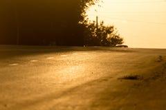 Väg för bilar på den guld- solnedgången Royaltyfria Foton