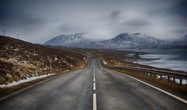 Väg i berg i mitt av vintern arkivbilder